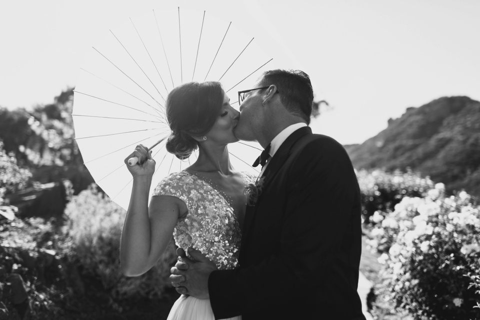 Couple kiss under parasol at saddlerock ranch