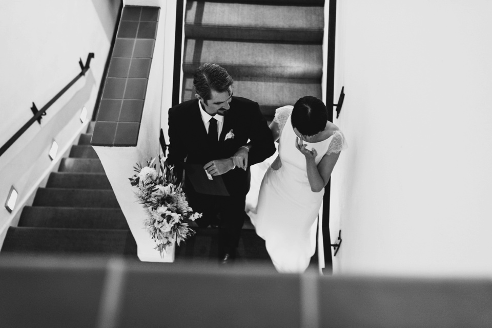bride is walked down the stairs by brother and cries