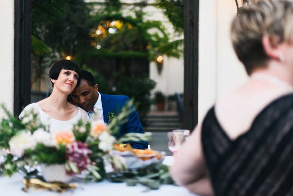 tender moment between bride and groom during toasts
