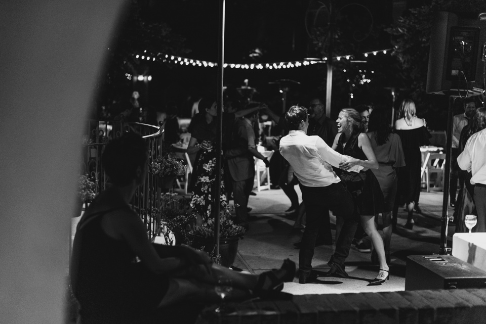 dancing shot of couple having fun as another guest looks on