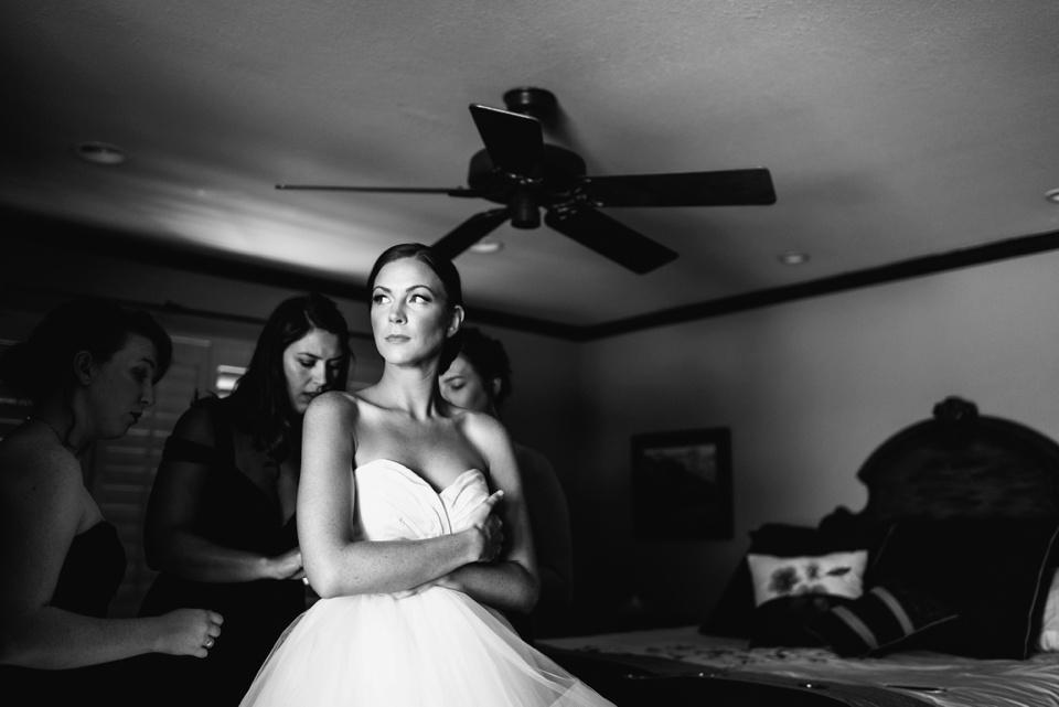 bride getting wedding dress on