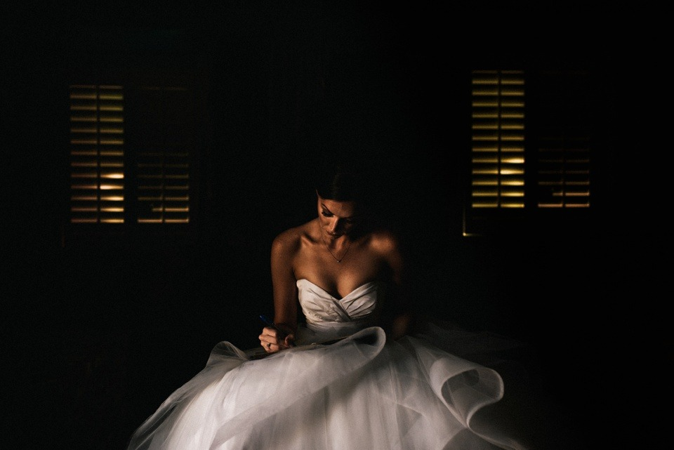bride writes letter in beautiful window light