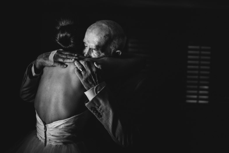 father of bride embraces daughter