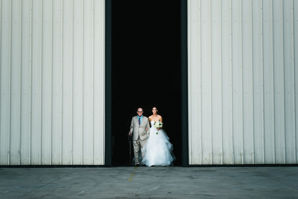 bride and dad exit aircraft hangar to ceremony