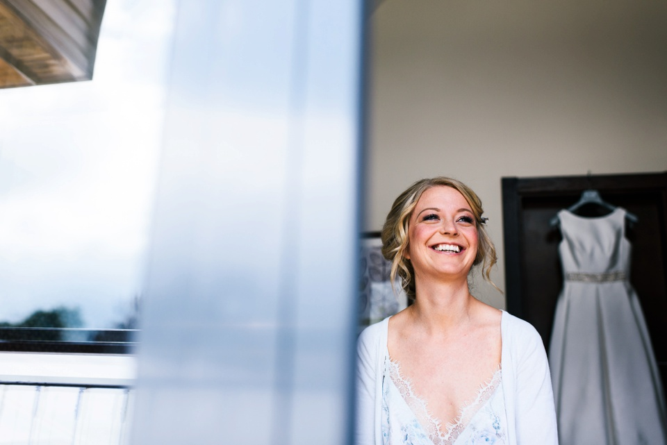 happy bride with dress hanging in background