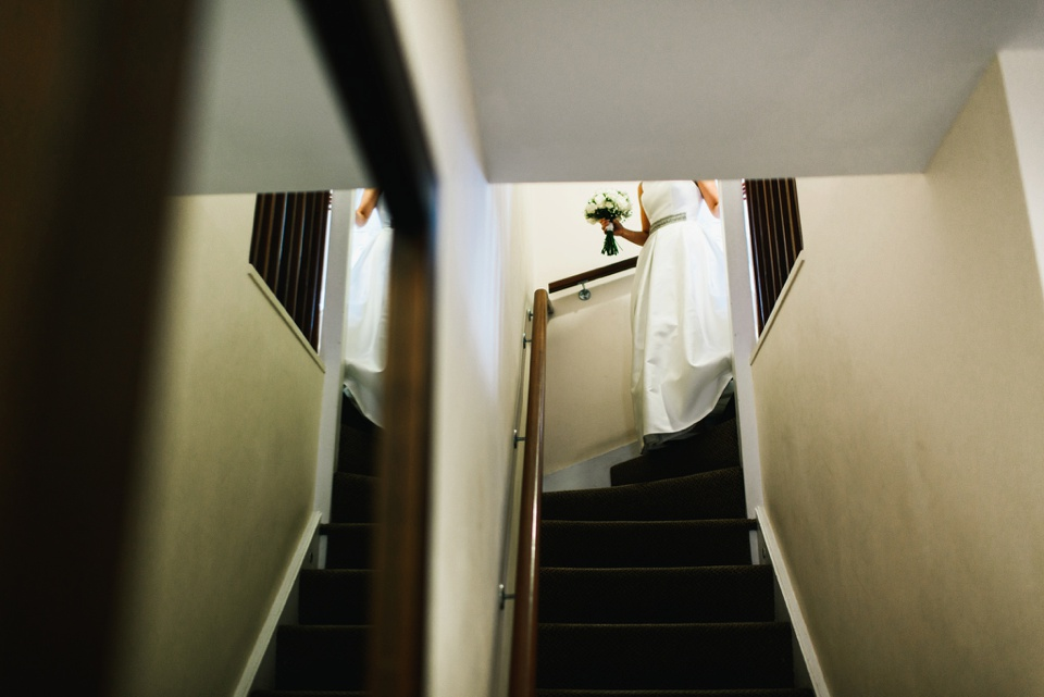 bride walks down stairs at northbrook park
