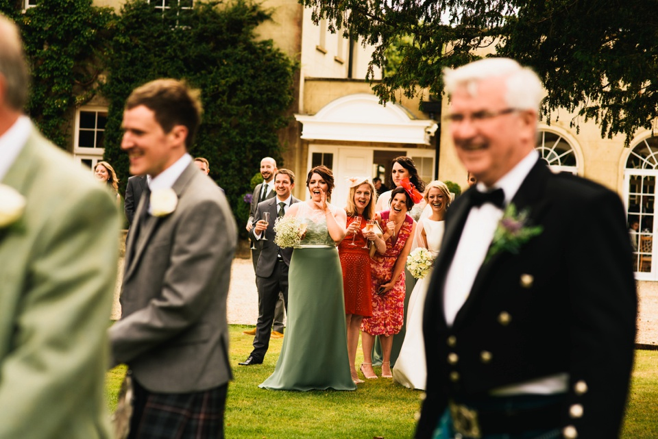 bridesmaids laugh at men wearing kilts