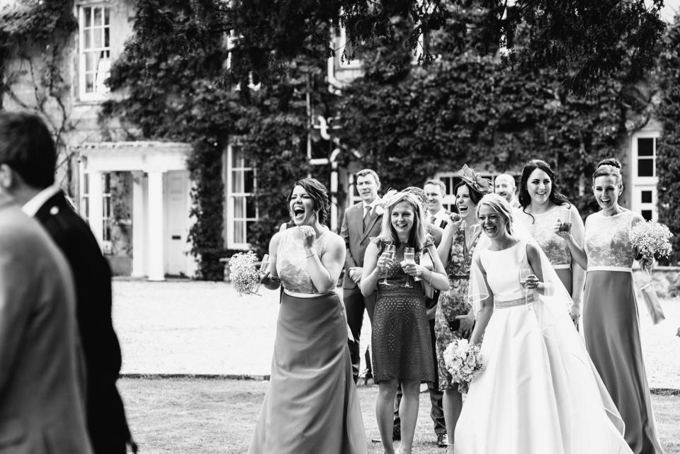 bridesmaids laugh at men wearing kilts