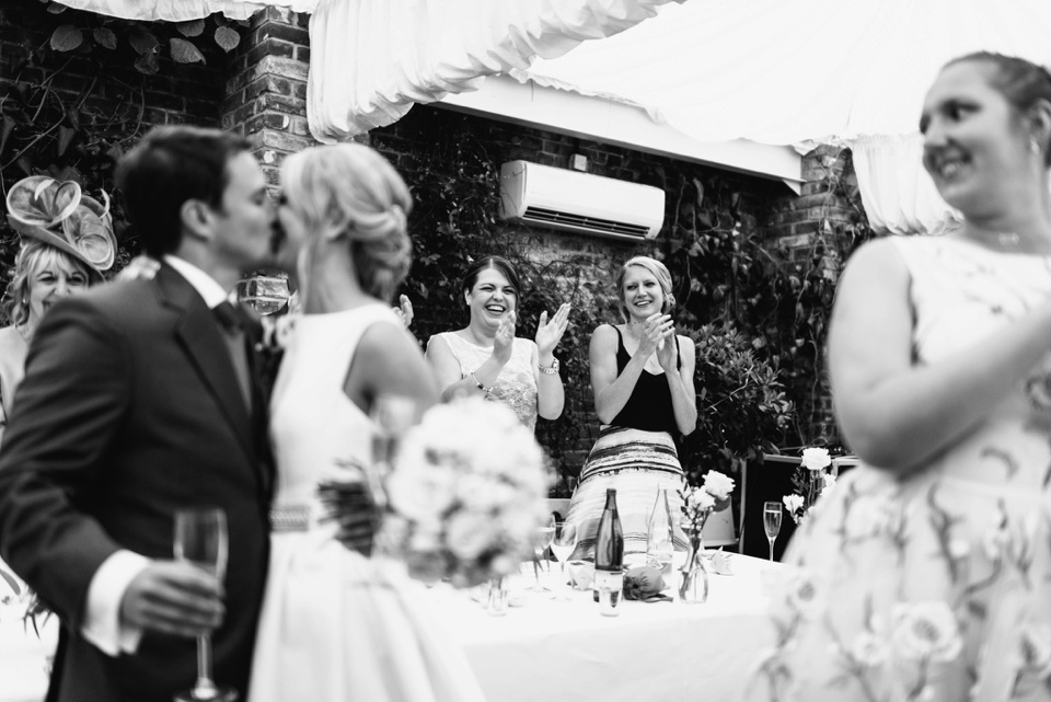 kissing couple as guests watch on