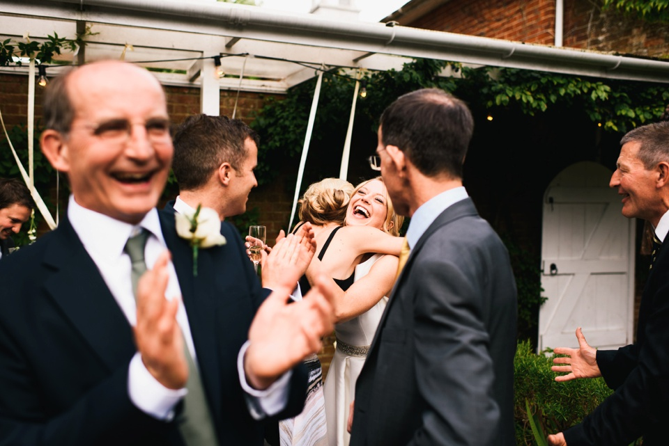bride embraces wedding guests