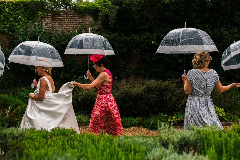 bride with friends and umbrellas