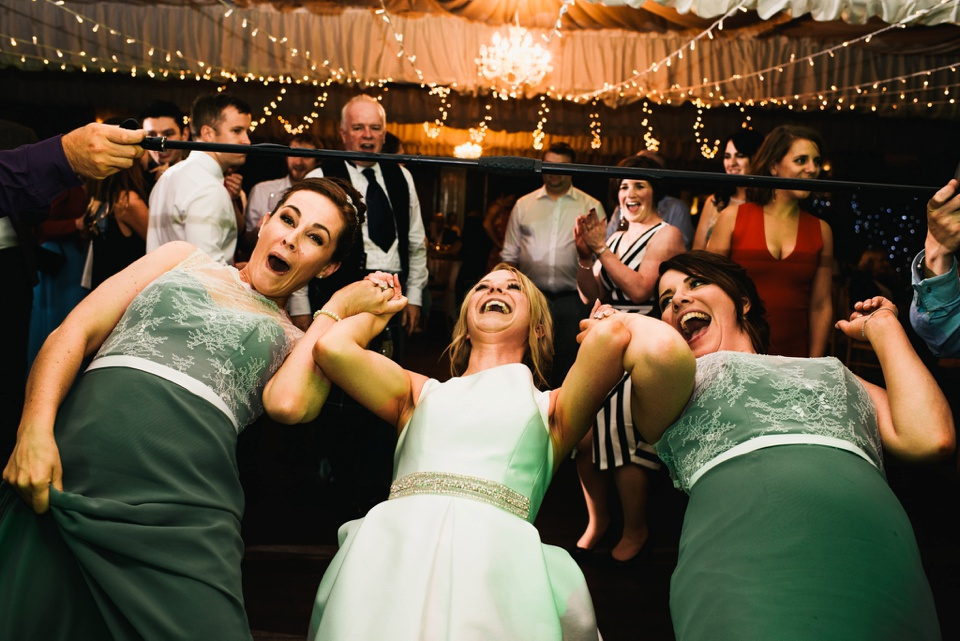 bride with bridesmaids on dance floor