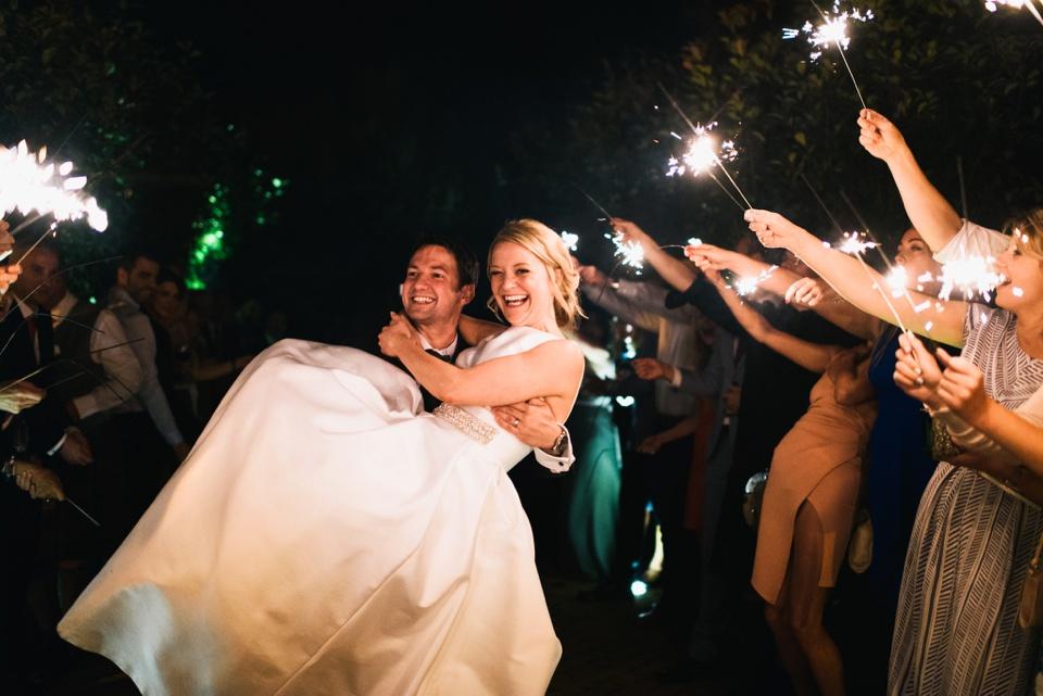sparkler exit groom carries bride