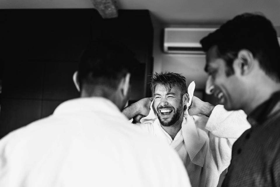 groom laughs with groomsmen