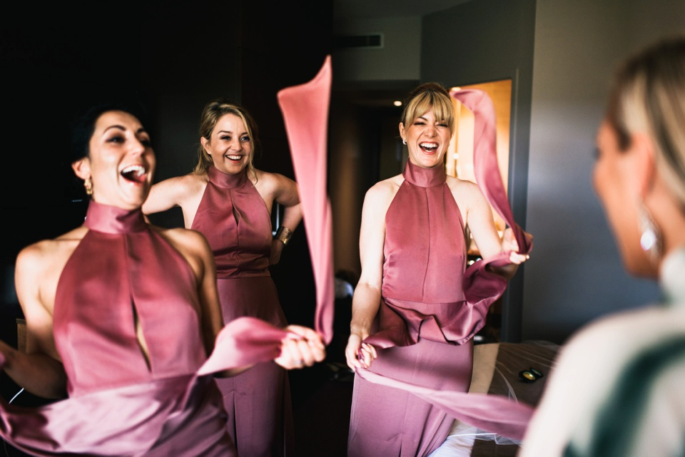 laughing bridesmaids in pink dresses