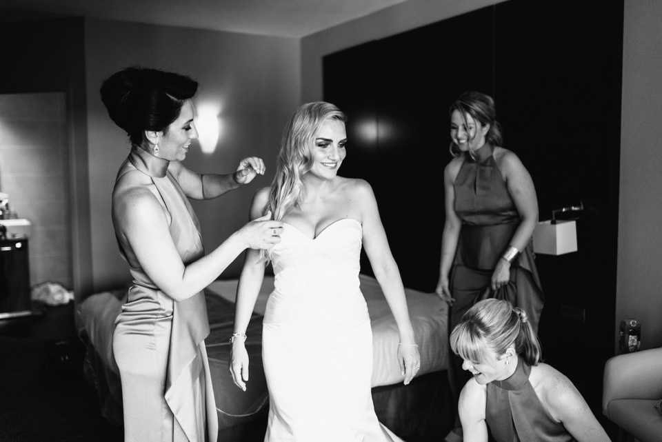 bridesmaids help bride put on wedding dress