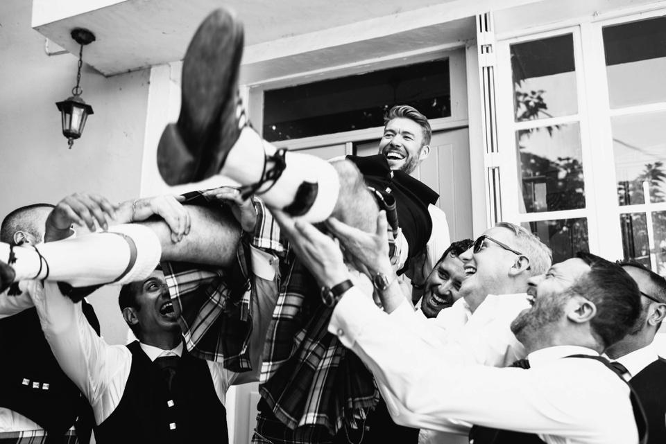 groomsmen throw groom in air