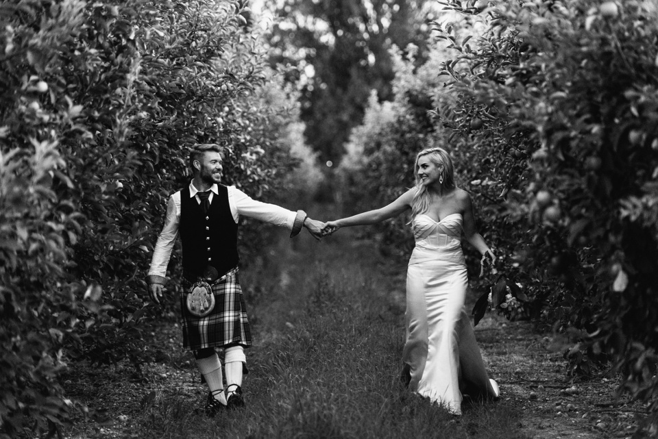 bride and groom hold hands walking through apple orchard.