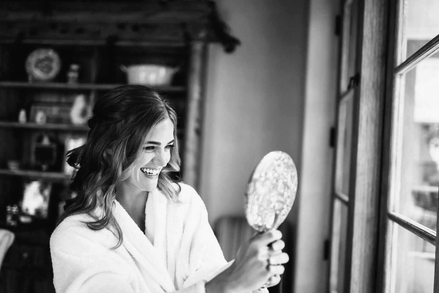bride smiles into mirror on wedding day - montecito wedding photography