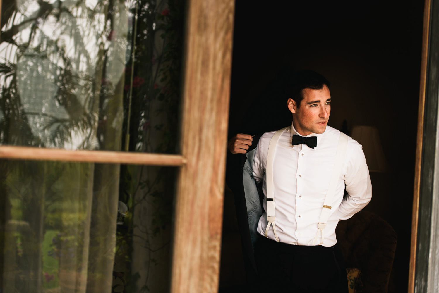 groom puts on wedding jacket - montecito wedding photography