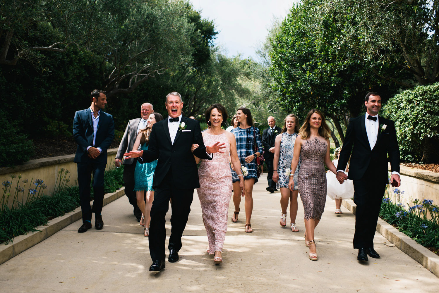 couples family follow close behind smiling and laughing - montecito wedding photography