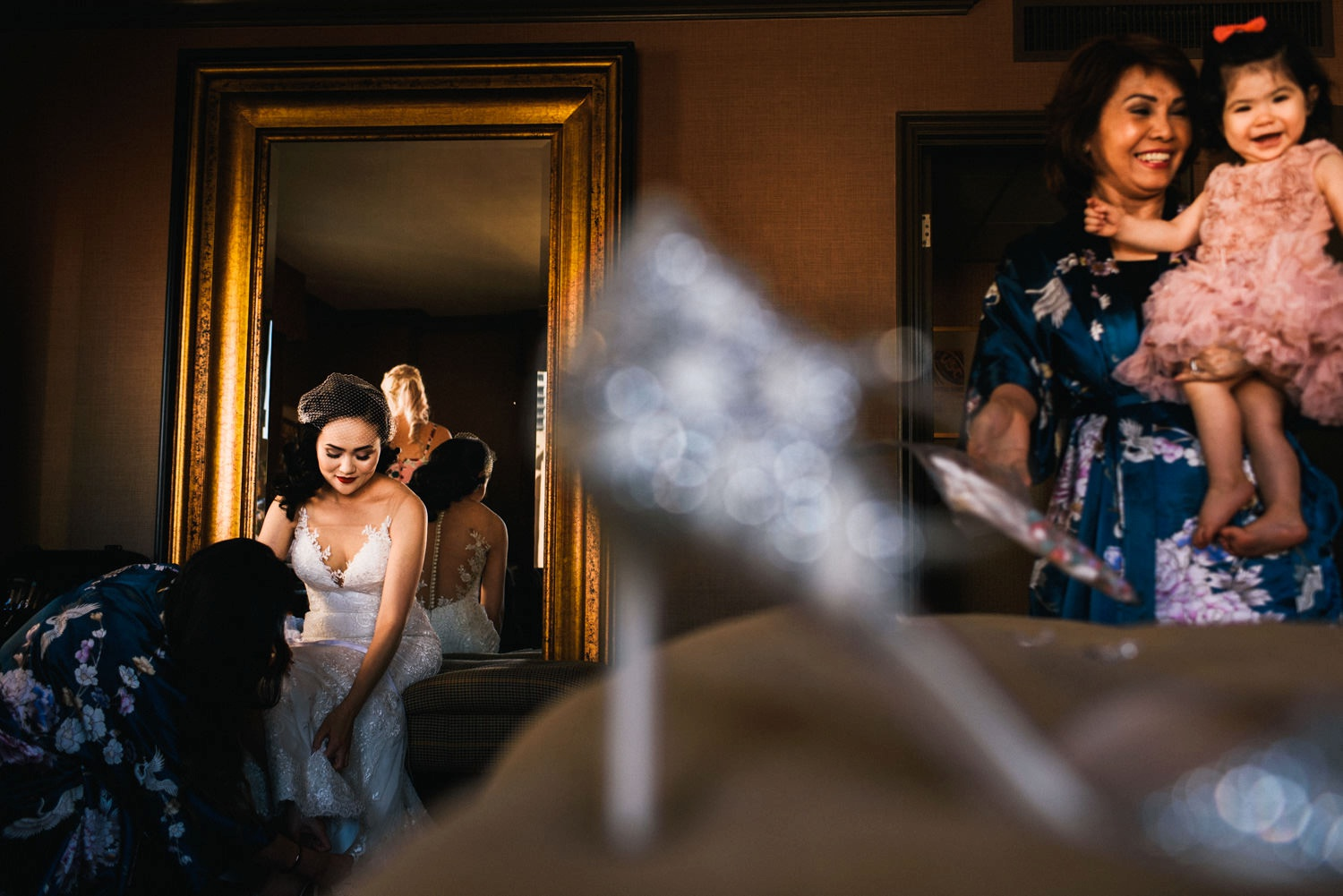 bride gets ready as daughter and mother laugh in background