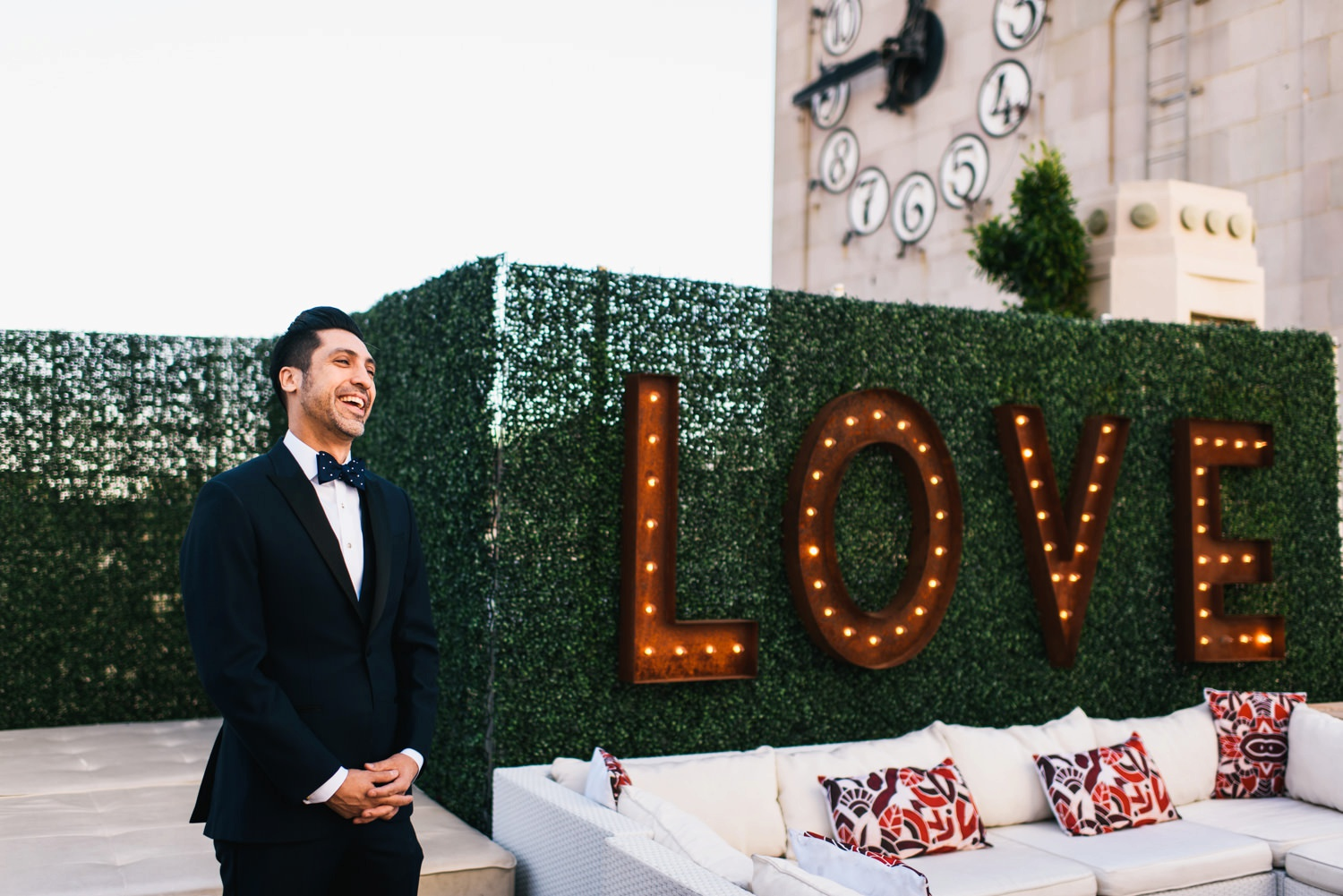 first look reaction by groom in front of love sign