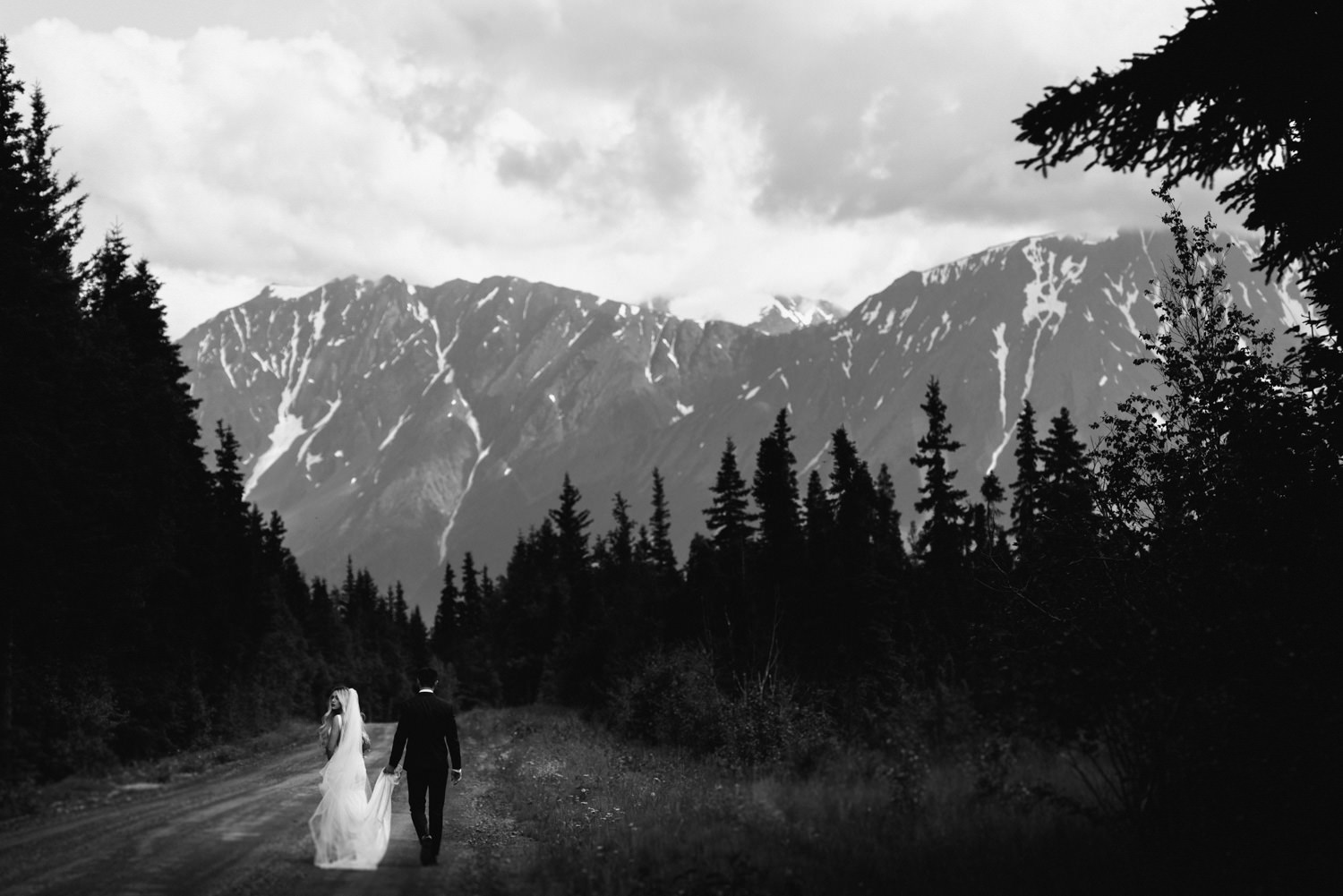 bride and groom walk down road in shadow of alaskan mountains